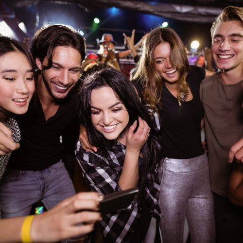 Cheerful friends looking at mobile phone while enjoying at nightclub during music festival